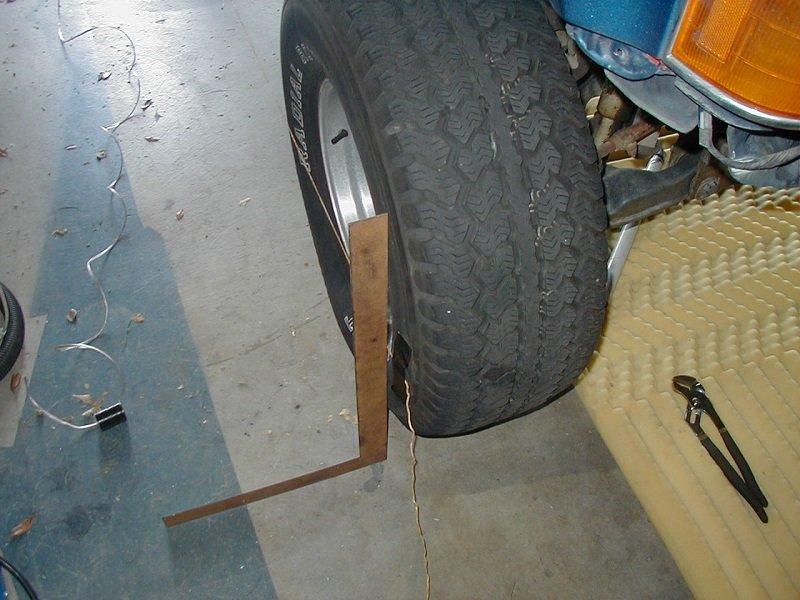 Đặt thước vuông góc với lốp xe để kiểm tra góc camber.